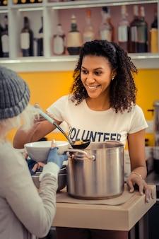 Giovane volontario. gioiosa bella donna che dà la zuppa mentre lavora nel centro di volontariato