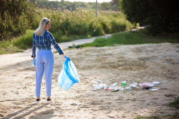 Giovane volontario raccogliendo bottiglie di plastica sulla spiaggia vicino al parco.