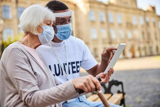 Giovane volontario in scudo protettivo e una signora anziana con un bastone da passeggio seduta su una panchina e guardando lo schermo del tablet