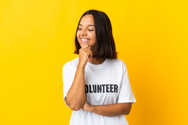 Giovane donna volontaria isolata sul giallo che osserva al lato e sorridente