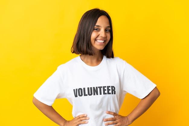 Giovane donna volontaria isolata su giallo in posa con le braccia al fianco e sorridente