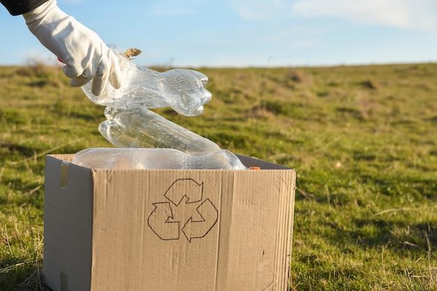 Giovani volontari che puliscono l'area nel parco, con tenere la bottiglia di plastica al parco pubblico. persone ed ecologia. raccolta di rifiuti di plastica in natura per il riciclaggio.