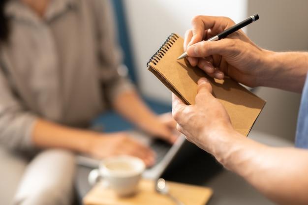 Giovane cameriere che tiene il blocco note e la penna sopra la pagina vuota mentre va a scrivere l'ordine del cliente