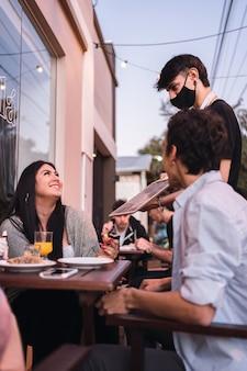 Un giovane cameriere che indossa una maschera in un bar consiglia il menu del giorno.