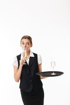 Giovane cameriera in uniforme che tiene vassoio con vetro pensieroso