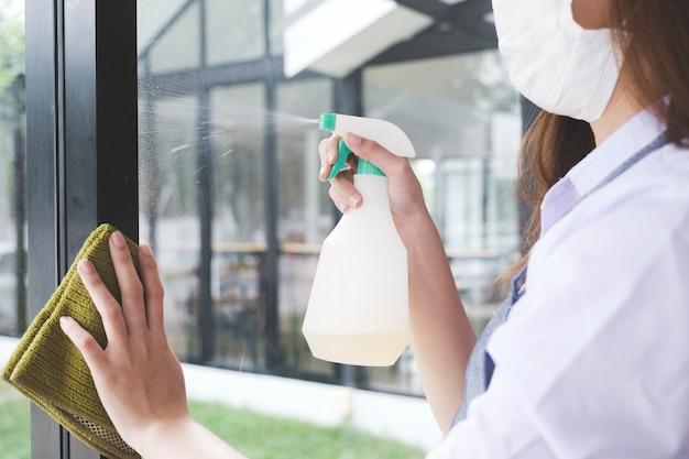 Giovane cameriera che indossa la maschera protettiva durante la pulizia e il lavoro in un caffè.