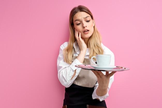 Giovane cameriera con vassoio in mano, preoccupata per qualcosa di isolato su sfondo rosa studio.