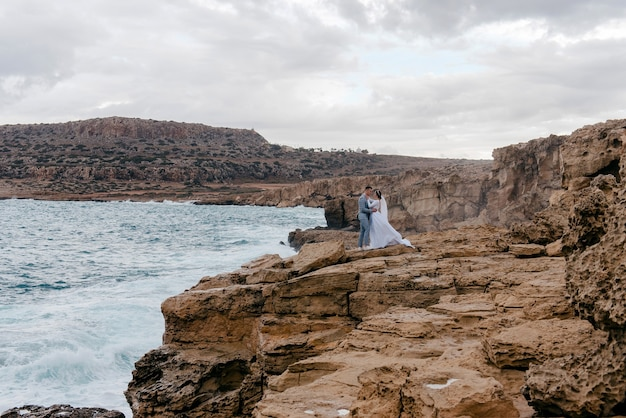 Giovani sposi, marito e moglie, abbracciati sugli scogli in riva al mare