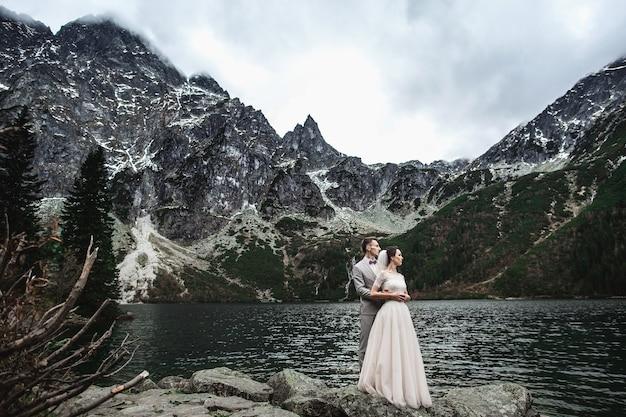 Giovani sposi in posa sulla riva del lago morskie oko, polonia, tatra