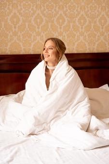 Giovane donna africana ben dormito che si sveglia a letto, sorridente e tenendo la coperta
