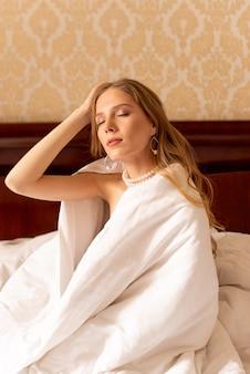 Giovani ben dormiti che si svegliano a letto, sorridendo e tenendo la coperta