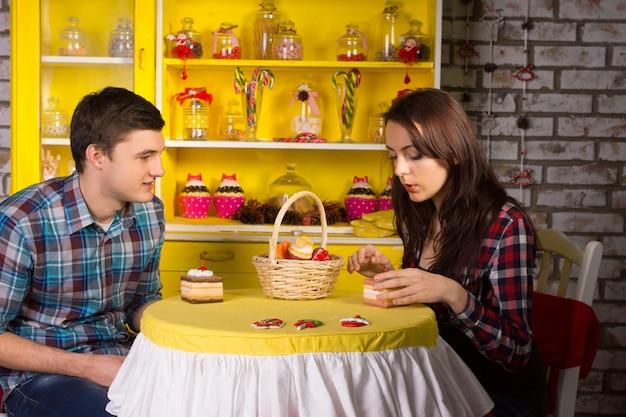 Giovane coppia bianca in top a scacchi incontri al cafe con pezzi di torta sul tavolo.