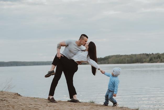 Giovane famiglia bianca con il figlio sulla spiaggia sulla sabbia in estate in riva al fiume