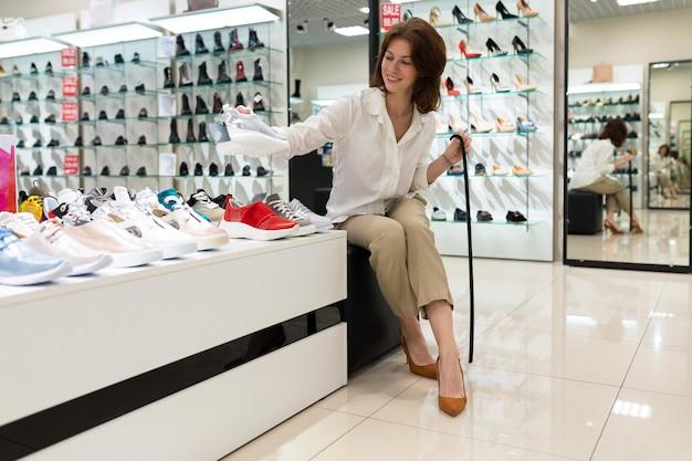 Giovane femmina bianca che si siede sulla sedia nell'angolo della scarpa al grande magazzino che sceglie le scarpe