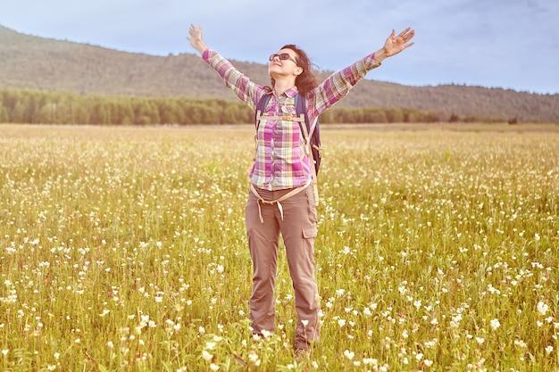 Giovane donna bianca che gode del sole e della libertà mentre si cammina in campagna.