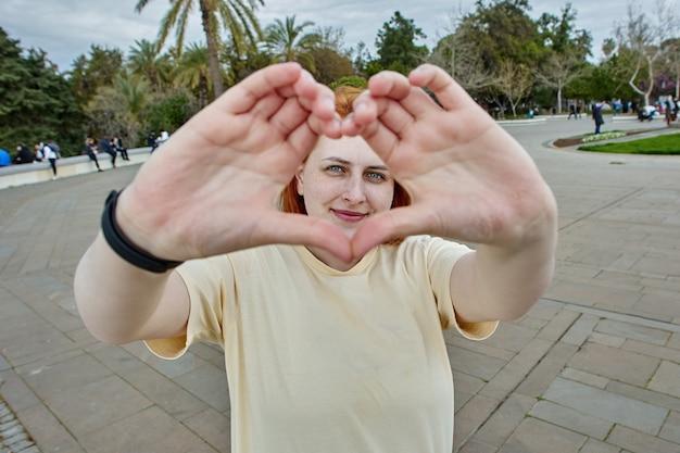 La giovane donna bianca fa la forma del cuore con le sue dita per la foto