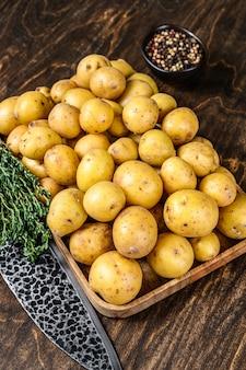 Giovani patate intere in un vassoio di legno