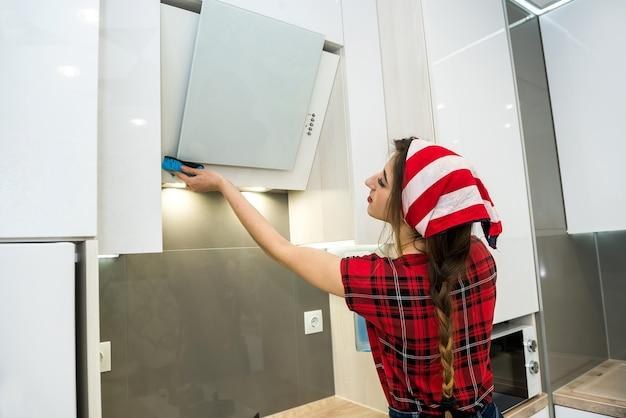 Giovane moglie pulizia cappa con straccio e detersivo in cucina. concetto di pulizia.