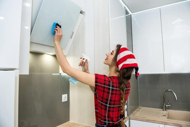 Giovane moglie pulizia cappa da cucina con straccio e detersivo in cucina. concetto di pulizie.