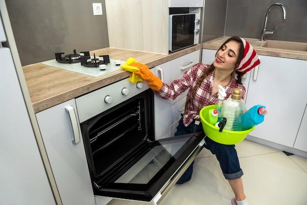 Giovane moglie che pulisce il forno con uno straccio giallo e spray in cucina.