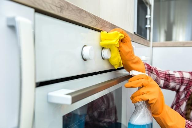 Giovane moglie pulizia forno con straccio giallo e spray in cucina.