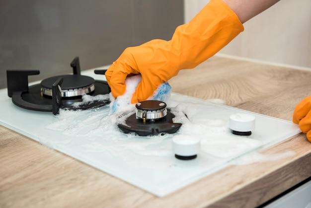 Giovane moglie pulizia forno con straccio giallo e spray in cucina. Foto Premium