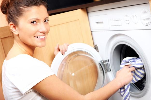 Una giovane moglie che mette un panno nella lavatrice