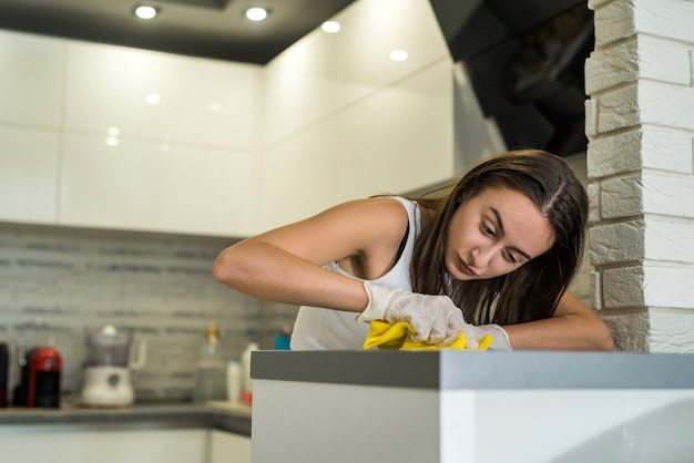 Giovane moglie in vestiti bianchi, guanti e straccio pulisce in cucina. pulizia domestica