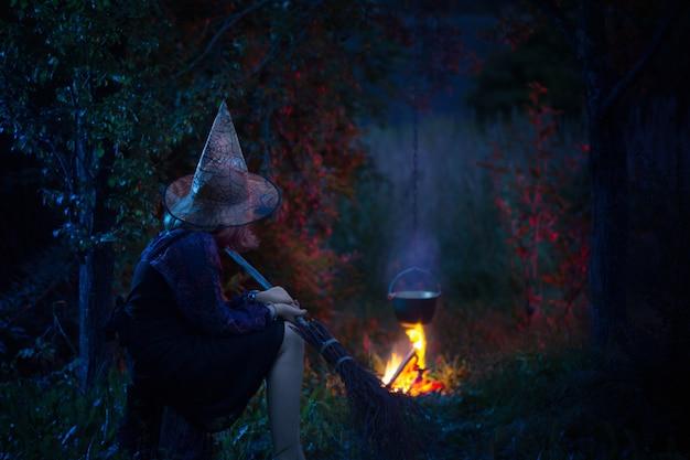 Giovane strega di fuoco nella foresta di notte