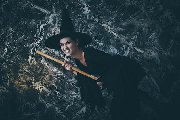 Giovane strega che vola sulla scopa