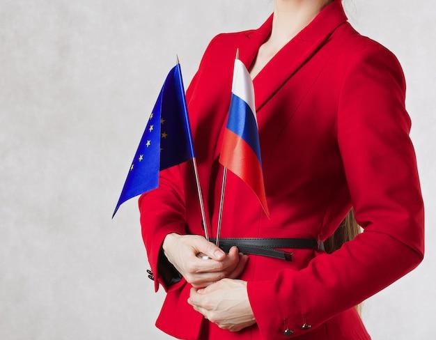 Una giovane donna tra i 30 ei 40 anni tiene in mano due bandiere dell'ue e della russia spazio libero per un testo