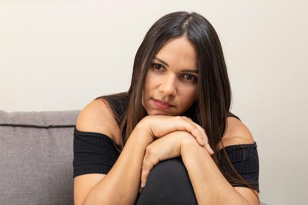 Giovane donna di 30 anni, seduta e riflessiva.