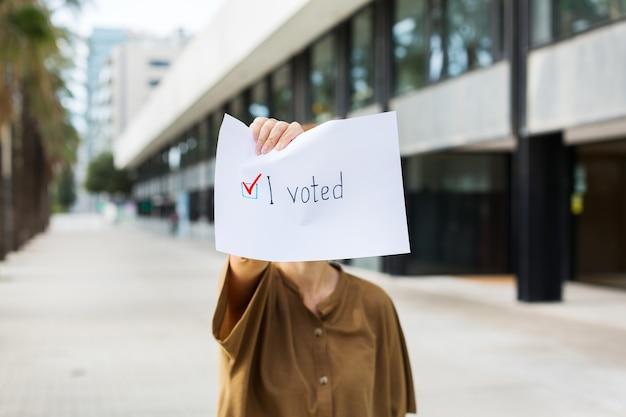 Giovane donna, attivista chiede di votare tenendo in mano la carta con la dichiarazione ho votato. attivismo politico, processo elettorale, concetto di posizioni di vita attiva. presidente, elezioni costituzionali.