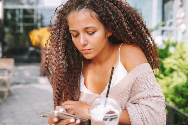 Giovane donna dipendente dalla tecnologia. smartphone di uso femminile che si siede al caffè e che beve bevanda.