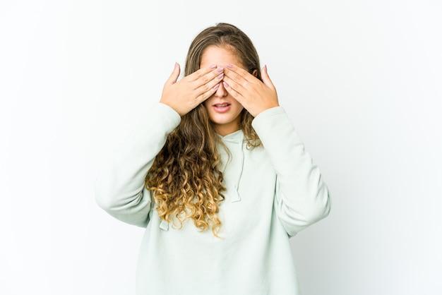 Giovane donna che copre gli occhi impauriti con le mani
