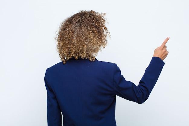 Condizione dell'afroamericano della giovane donna e indicare l'oggetto sullo spazio della copia, retrovisione contro la parete piana