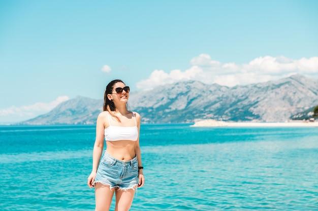 Giovane donna sola lungo il mare blu con le montagne sullo sfondo