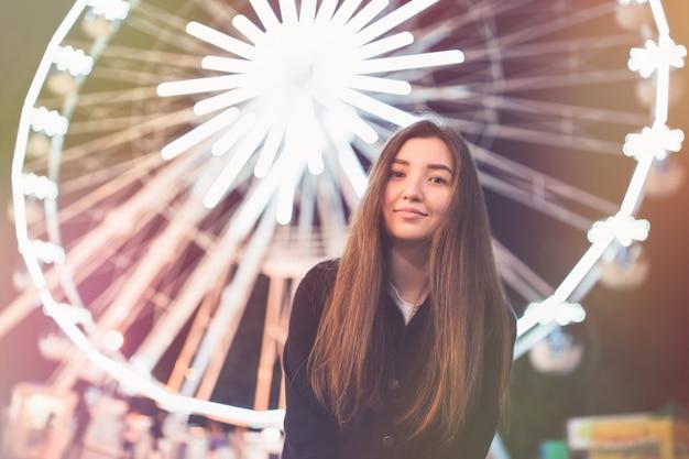 Giovane donna nel parco di divertimenti di notte ruota panoramica sullo sfondo