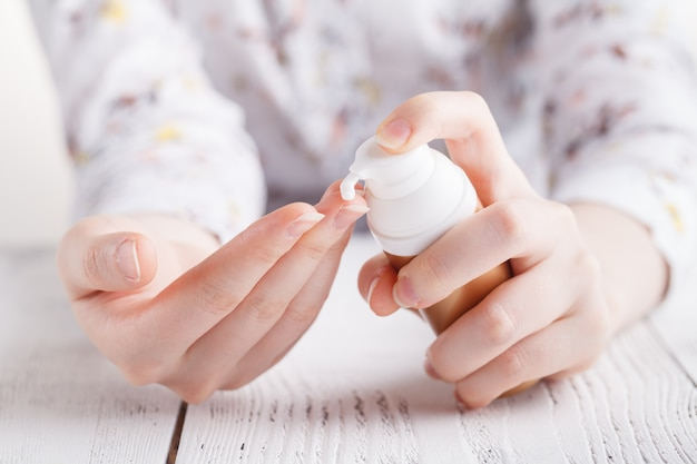 La giovane donna applica la crema sulle sue mani.