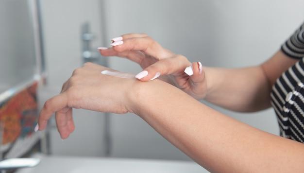 Giovane donna che applica crema per il corpo a portata di mano in bagno.