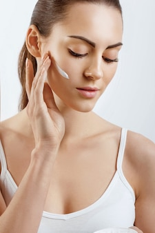 Giovane donna che applica la crema alla sua faccia skincare e cosmetici