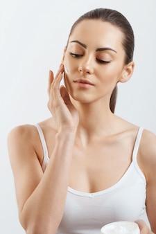 Giovane donna che applica la crema al viso