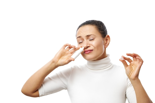 Giovane donna che applica spray nasale che propone alla macchina fotografica isolata sulla superficie bianca con lo spazio della copia