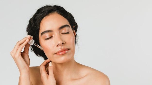 Giovane donna che si applica il siero sul viso