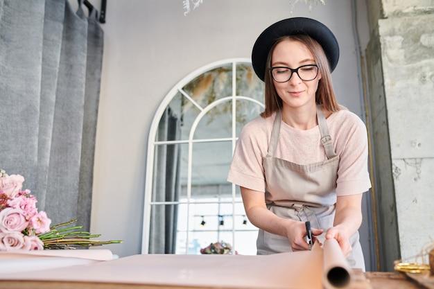 Giovane donna in grembiule e cappello che tagliano pezzo di carta da imballaggio mentre facendo i mazzi floreali in studio