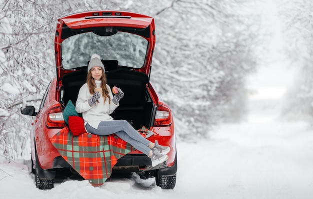 La giovane donna è seduta in una macchina nella foresta invernale e beve caffè