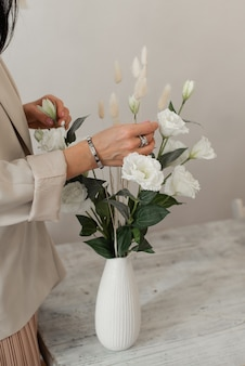 La giovane donna organizza un tavolo da pranzo con i fiori. fiori bianchi in un vaso.