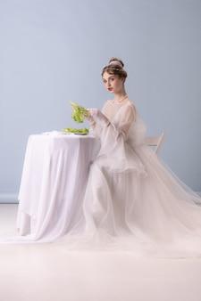 Giovane donna in azione artistica isolata sul muro bianco. stile retrò, concetto di confronto di epoche. bellissimo modello femminile come principessa, regina o duchessa, vecchio stile.