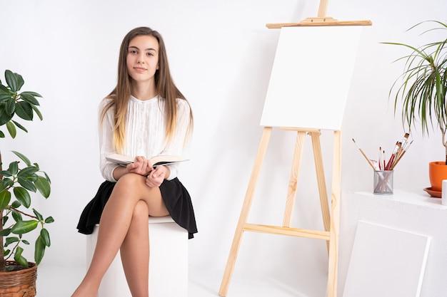 Giovane donna in studio d'arte con libro su sfondo bianco