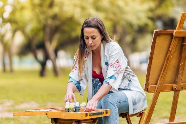 Artista di giovane donna che dispone vasi di vernice su un tavolo mentre è seduto di fronte a una tela nel parco.